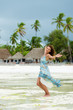 Happy cheerful girl posing on the white sand beach.African village in the background