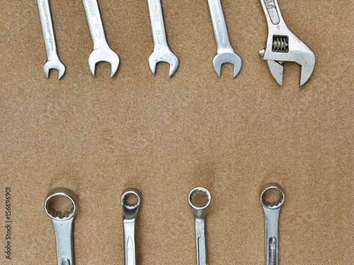 a various wrench spanners tools on wood background