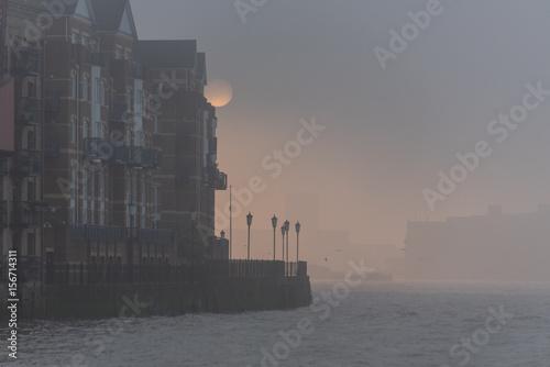 Photo  Luna piena scompare dietro un edificio nella nebbia serale del tamigi a londra