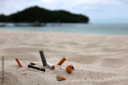 Vászonkép  Cigarette butts and the ashtray on the beach.
