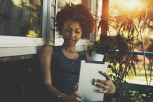Thoughtful Young Biracial Female Is Holding Digital Tablet While Sitting On The Bench Near Summer House, Afro American Teenage Girl Is Reading EBook Near Wall Of Her Cottage In Tropical Resort