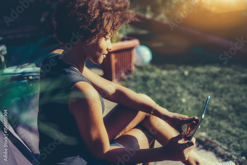 Side view of young sexy afro american girl sitting in park bench and talking wit Canvas-taulu