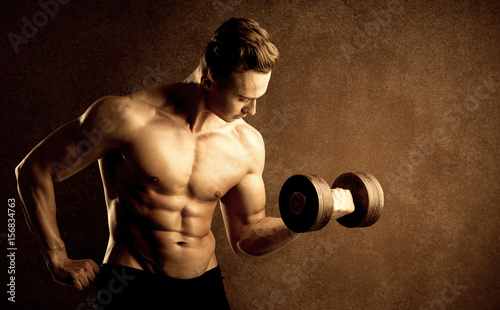 Muscular fit bodybuilder athlete lifting weight