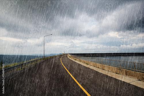 Cuadros en Lienzo falling rain in road on the ridge of Lam Takong reservoir dam, Thailand