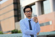 Portrait of handsome young Asian business man holding mobile smart phone and looking on camera at outside office background.