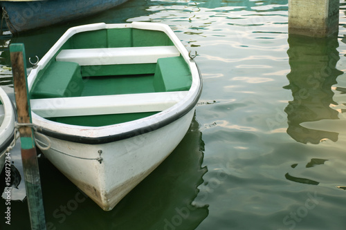White rowboat moored near shore Canvas Print