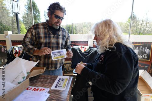 Organizer Chris Cox offers merchandise to Pam Holman during