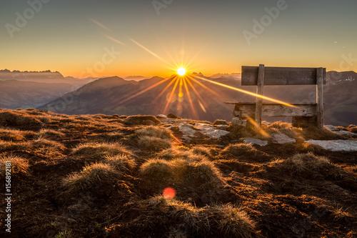 Foto op Plexiglas Ochtendgloren Sonnenaufgang am Berg mit Sitzbank