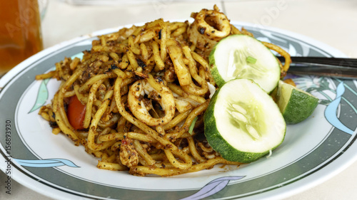 Photo  Mee Goreng with sliced cucumber and lemon on the plate