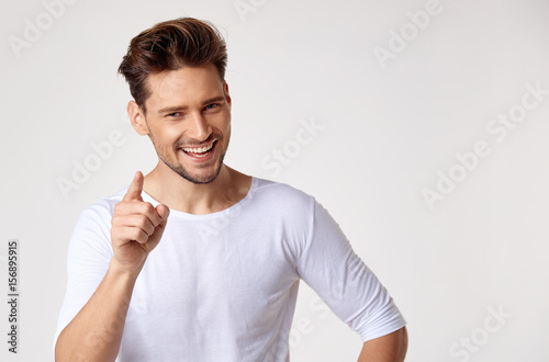 Handsome young man pointing something