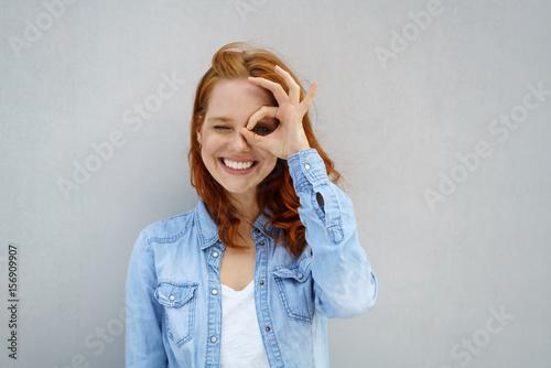 Fotografia lachende frau schaut durch ihre finger