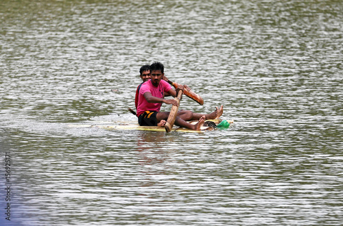 Two Boys Use Cricket Bats To Paddle A Handmade Boat On Flooded Road In