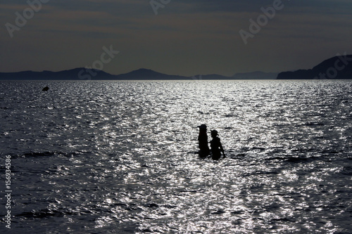 Photo two women silhouetted in the sea at sunset