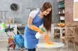 Beautiful woman cleaning table at home