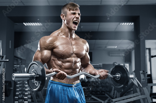 Muscular man working out in gym doing exercises, strong male naked torso abs