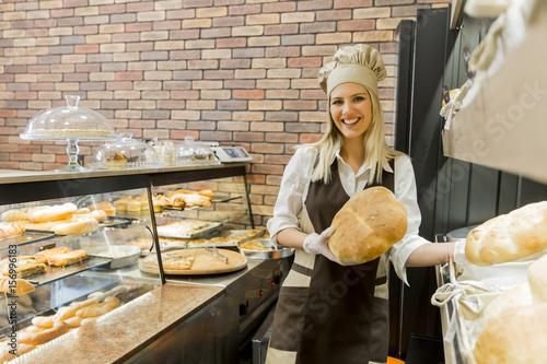 Foto op Plexiglas Bakkerij Young woman takes fresh bread from the shelves in a baker shop
