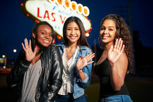 Group Of Three Young Girls On Vacation Waving In Front Of Welcome To Las Vegas Sign At Night