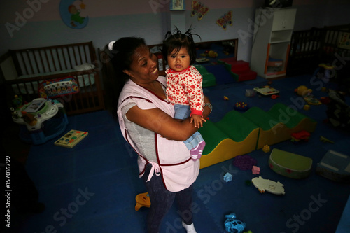 An inmate carries a child at a nursery school inside Santa