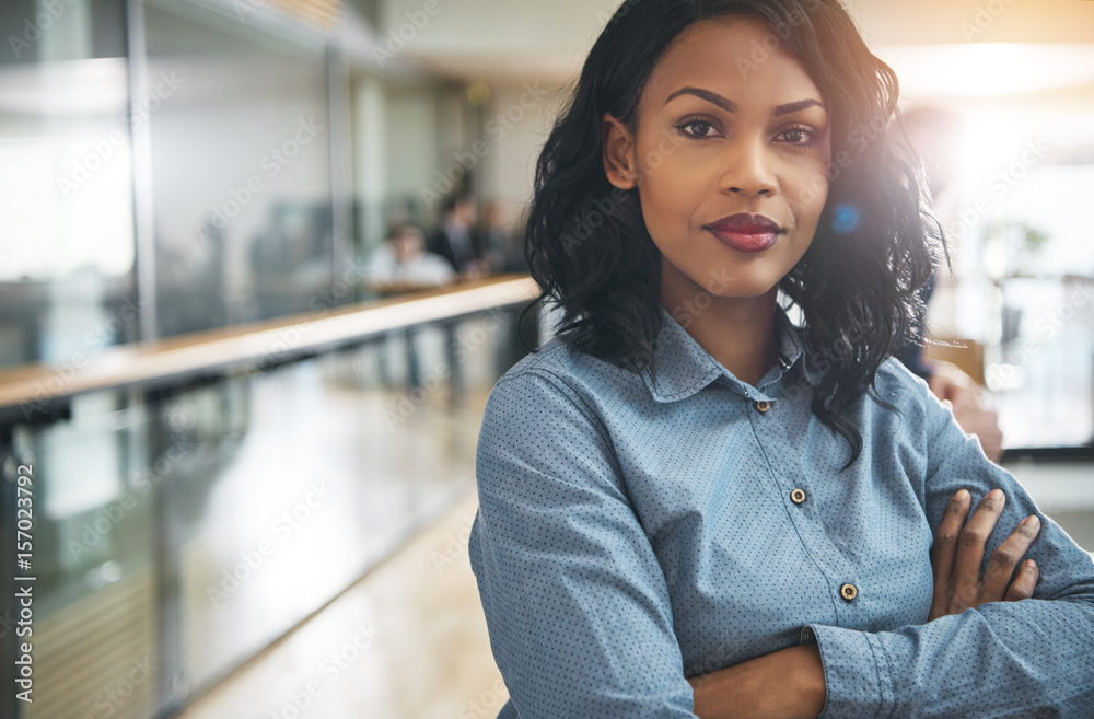 Fototapeta Beautiful black businesswoman with arms crossed in office