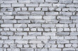 Fragment of old brick fence whitewashed by lime, relief surface and natural background