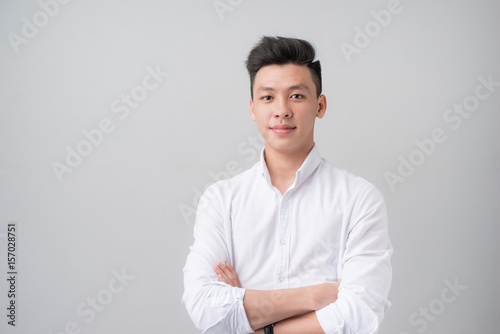 Fotografia  Portrait of good looking asian man over gray background.