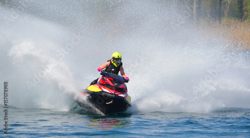 Photo Stands Water Motor sports Jet Ski racer cornering at speed creating at lot of spray.