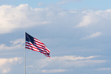 Horizontal Image Of The American Flag  Against A Sky With Thick White And Gray Cumulus Clouds And Blue Sky. Flag Is Unfurled In The Breeze.