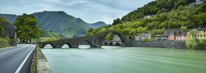 panorama with bridge and green river in Italy