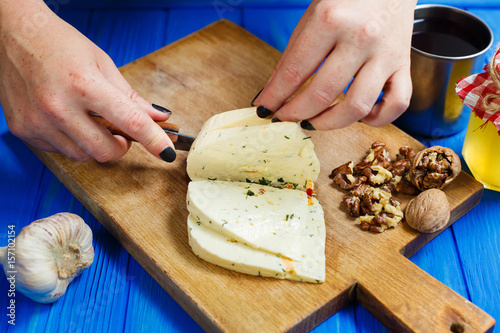 Staande foto Zuivelproducten Woman hands cutting spicy homemade cheese on cutting board, serving with walnuts and honey, front view