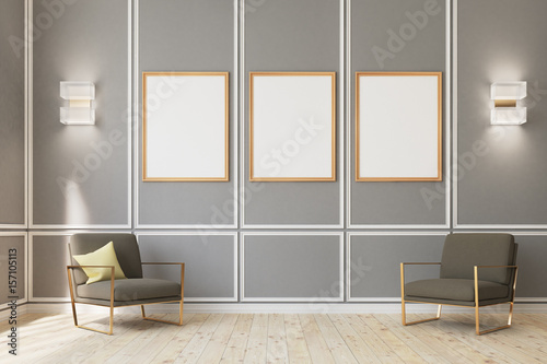 Photo Three framed posters on gray wall, armchairs