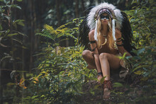 American Indian Woman In Native Traditional Dress,posing In The Wild Forest