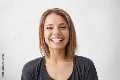 Positive human facial expressions and emotions. Cheerful attractive teenage girl with bob hairstyle grinning broadly, showing her perfect white teeth at camera while spending nice time indoors