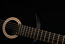 Part Of A Black Six-string Classical Acoustic Guitar Isolated On Black Background.
