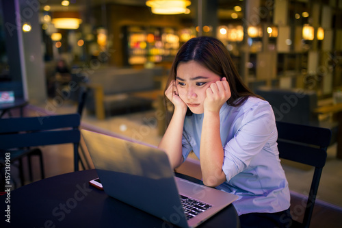 Láminas  Woman  using laptop in night time at cafe  she feel worried