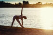 Silhouette of a Young woman doing yoga exercises on the lake beach at sunset