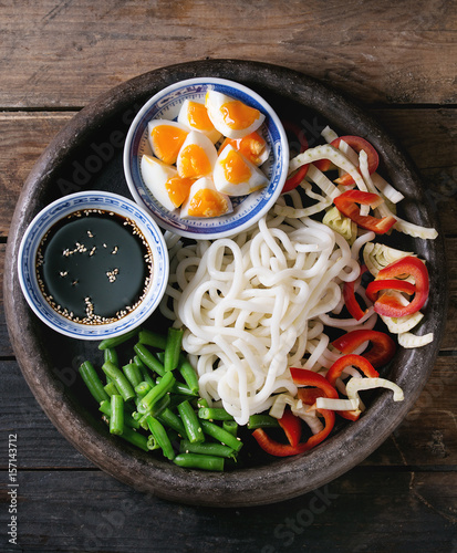 Photo  Ingredients for cooking stir fry udon noodles, green beans, sliced paprika, boiled eggs, soy sauce with sesame seeds in traditional bowls in terracotta tray over old wooden background