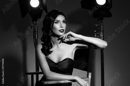 Young pretty beautiful woman in red long evening dress with makeup, red lips and classical hollywood waves hairstyle sitting in director's chair at film set with two cinema lights Canvas Print