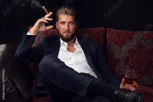Obraz na plátně  Erfolgreicher Geschäftsmann entspannt bei Zigarre und Wein
