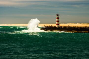 FototapetaMała latarnia morska w obliczu wielkiej fali.
