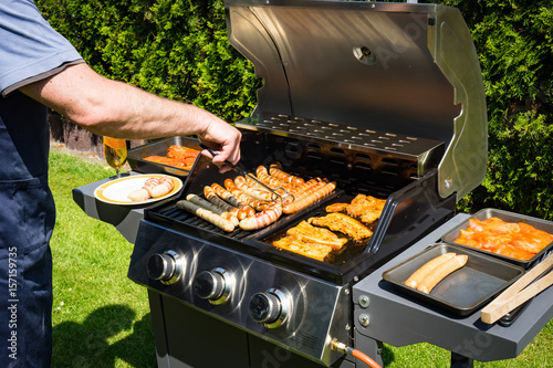 Spoed Foto op Canvas Grill / Barbecue Grillsaison - Mann beim grillen am Gasgrill