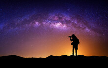 Silhouette Of Photographer With Camera And Milky Way Blackground.