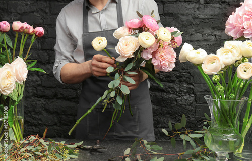 Male florist creating beautiful bouquet in flower shop, close up