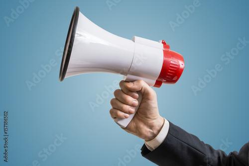 Announcement concept. Hand holds megaphone. Canvas Print