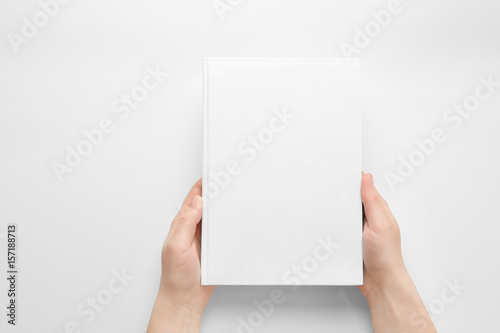 Fotografering  Female hands holding closed book with blank cover on light background