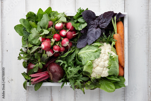 Foto op Plexiglas Groenten Fresh vegetables and herbs in wooden box on white table, top view