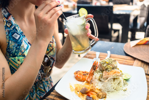 Woman guest eating seafood and drinking cocktail in restaurant