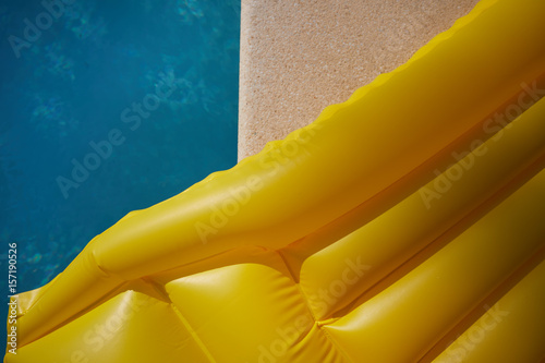 Fotografie, Obraz  An inflatable yellow air mattress swimming in a shiny blue swimming pool