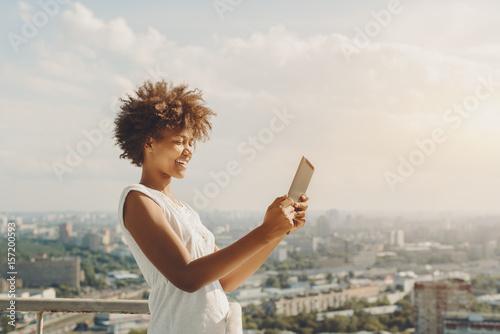 Valokuva  Laughing beautiful afro american teenage girl is making panorama image on her di