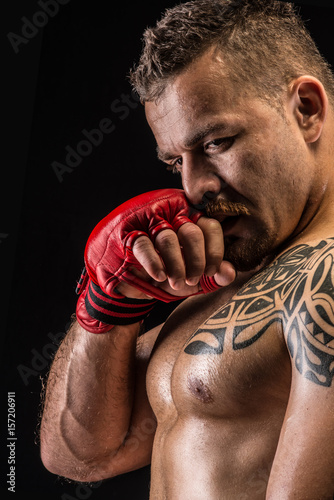 Muscular fighter posing with boxing gloves Canvas Print