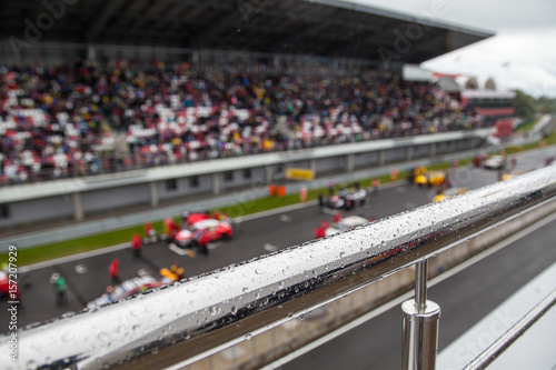 Racing cars on the starting grid. The focus on the handrail with rain drops